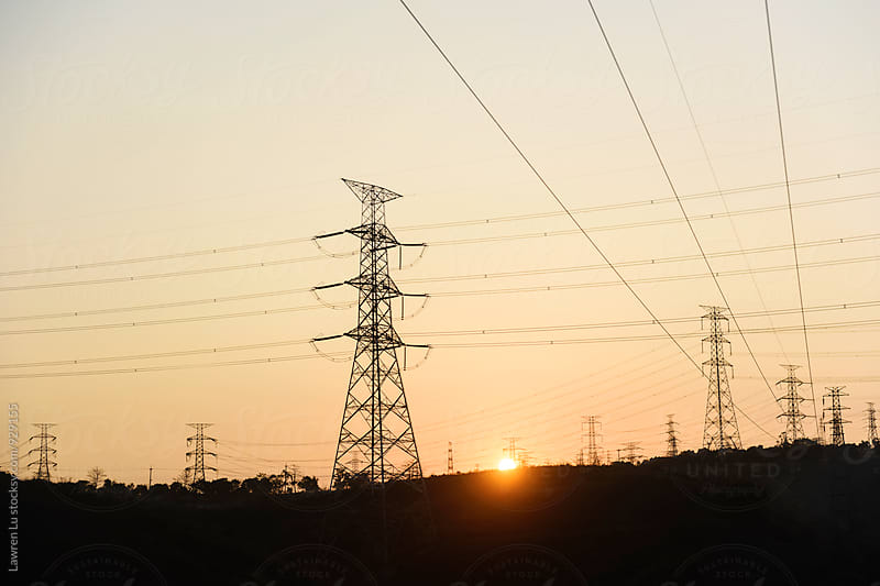 Setting sun behind electricity pylons by Lawren Lu for Stocksy United