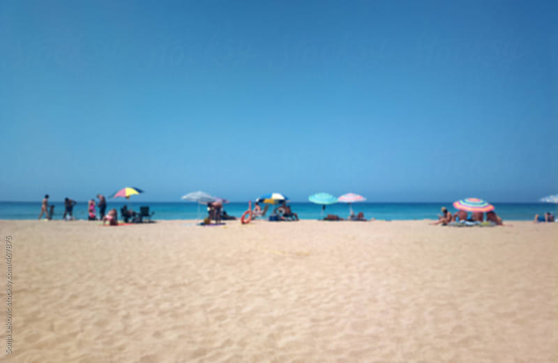 sandy beach and blue sky with people in blur by Sonja Lekovic for Stocksy United