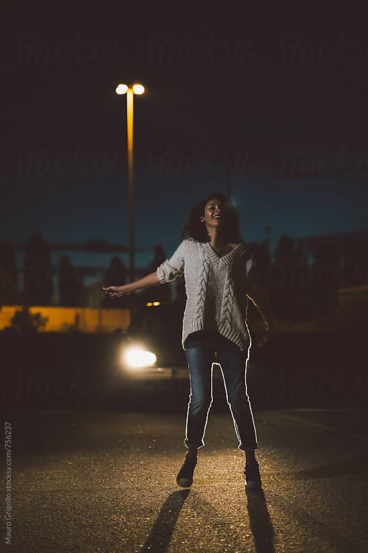 Happy woman dancing in front of a car  by Mauro Grigollo for Stocksy United