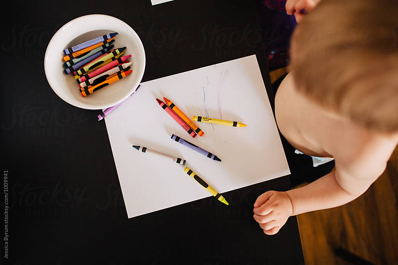 Overhead image of a toddler at a table with crayons and paper. by Jessica Byrum for Stocksy United