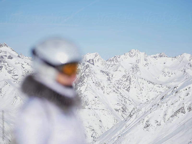 person in ski clothing in front of snowy moutain range by rolfo for Stocksy United