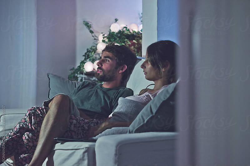 Young couple watching movies at home. by BONNINSTUDIO for Stocksy United