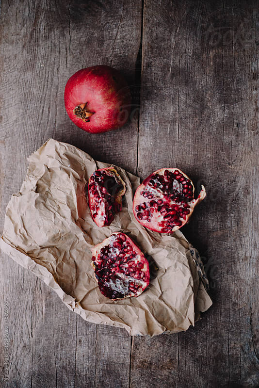 Pomegranates on a wooden background by Natasa Kukic for Stocksy United