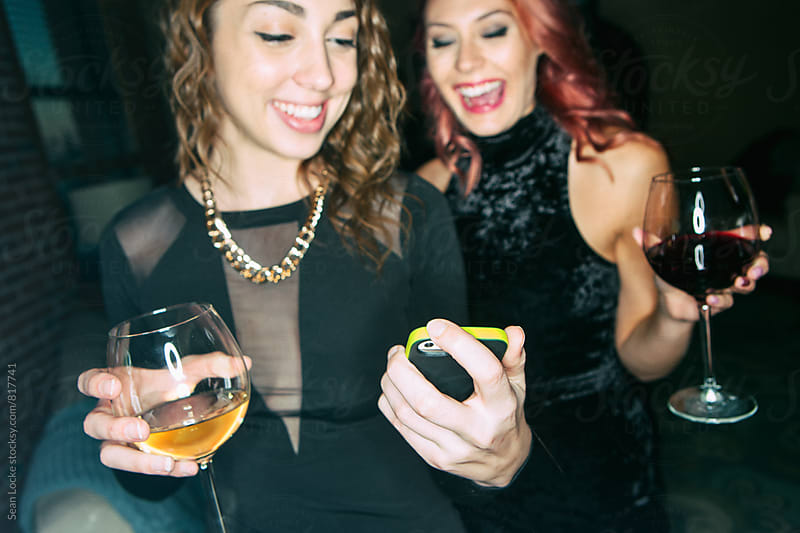 NYE: Friends Looking At Cell Phone During Party by Sean Locke for Stocksy United