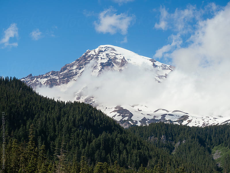 Clouds in front of snow covered Mt. Rainier with pine trees. Washington State. by Jeremy Pawlowski for Stocksy United