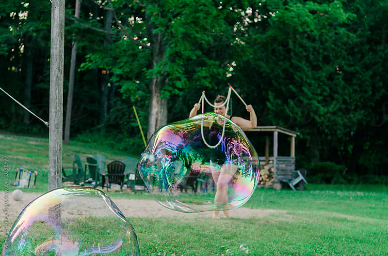 woman creates large bubbles by Margaret Vincent for Stocksy United