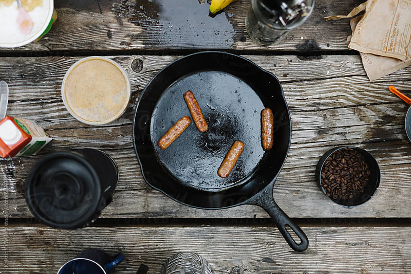 Sausage in a cast iron pan sitting on a picnic table by Kristine Weilert for Stocksy United