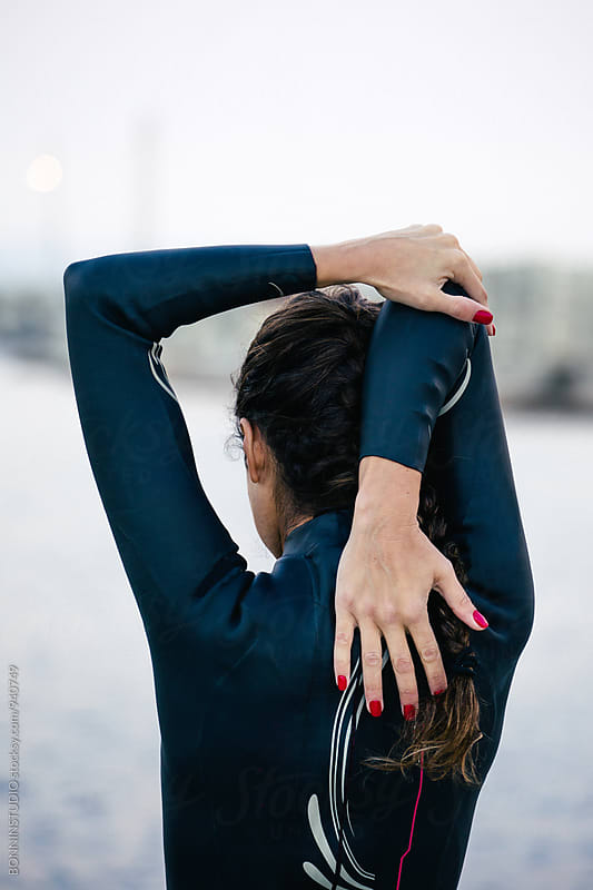 Back view of a woman wearing a wetsuit doing stretching exercise. by BONNINSTUDIO for Stocksy United