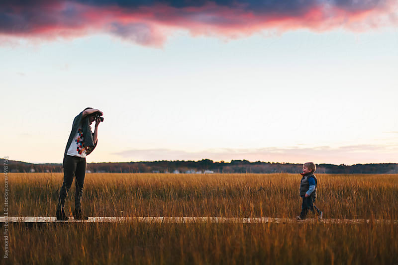 Woman Photographing Toddler on Boardwalk in Marsh by Raymond Forbes LLC for Stocksy United