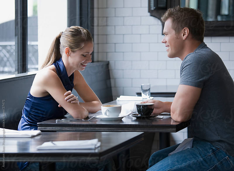 Young couple talking in cafe by Andersen Ross Photography for Stocksy United