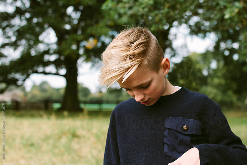 Portrait of a blonde teenage boy, outdoors. by Helen Rushbrook for Stocksy United