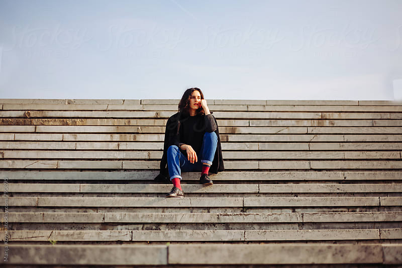 Woman sittin on the stairs - horizontal by Marija Kovac for Stocksy United