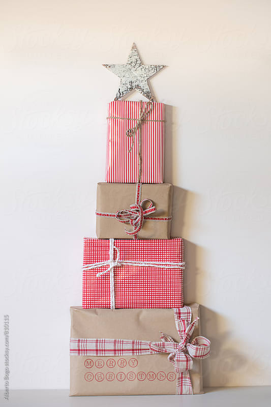 Three brown paper wrapped gifts laid out in the shape of a Christmas tree  by Alberto Bogo for Stocksy United