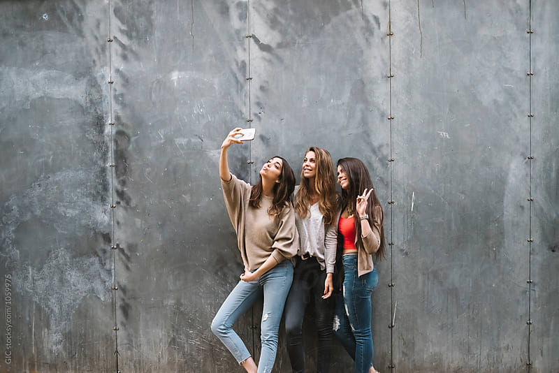 Three happy women taking a selfie with the phone by Simone Becchetti for Stocksy United