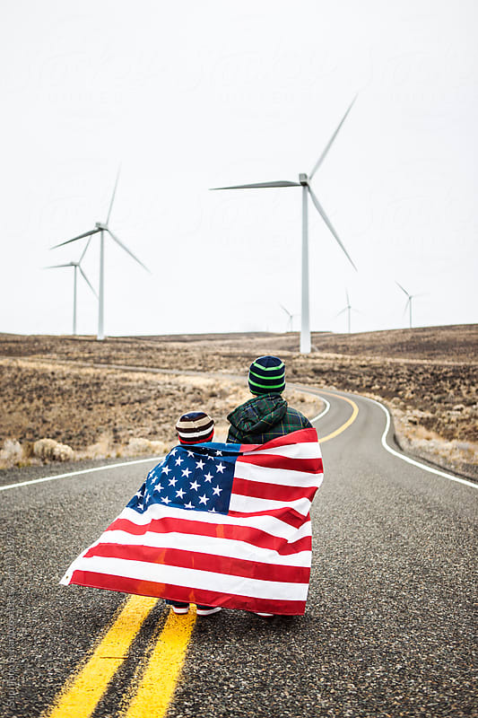 Two little boys with American flag standing near wind farm by Suprijono Suharjoto for Stocksy United