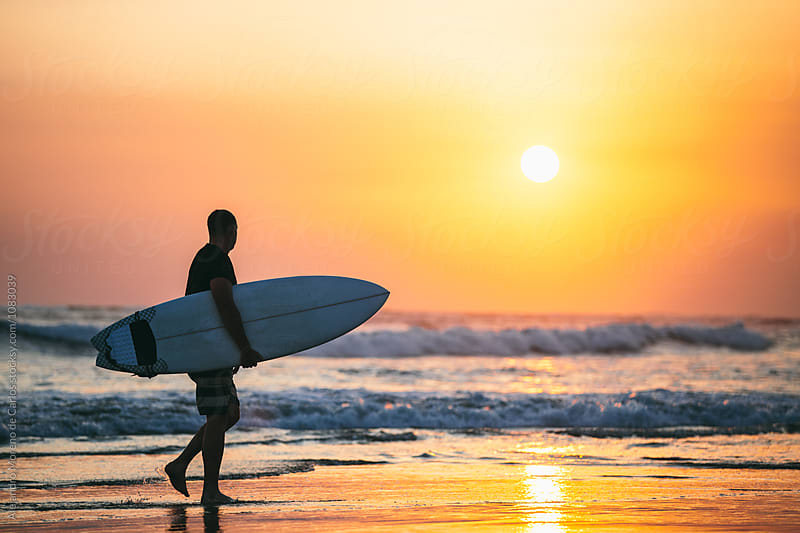 Man carrying surfboard along beach at sunset by Alejandro Moreno de Carlos for Stocksy United