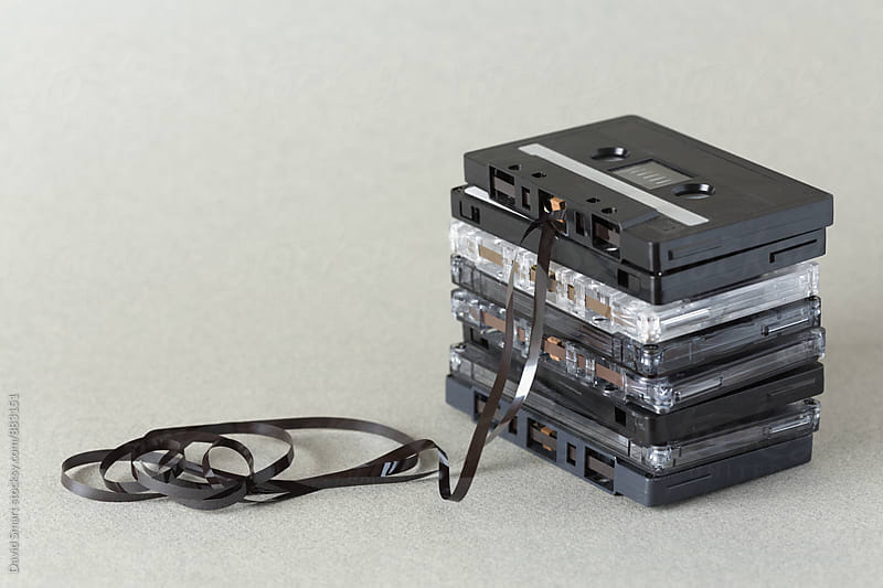 Stack of audio cassette tape with loose tape spilling from top cassette. by David Smart for Stocksy United