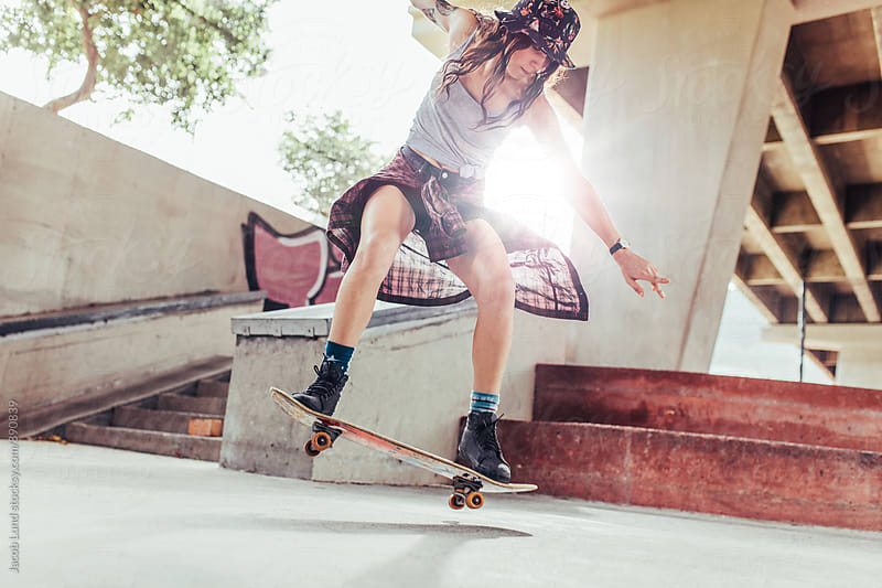 Young girl doing tricks on skateboard in skate park by Jacob Lund for Stocksy United