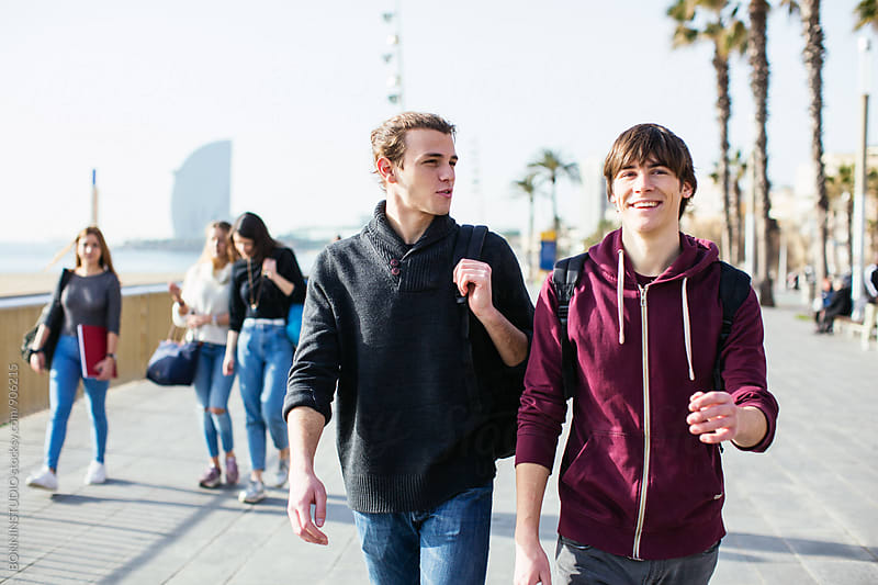 Teen students talking whilst walking on the street. by BONNINSTUDIO for Stocksy United