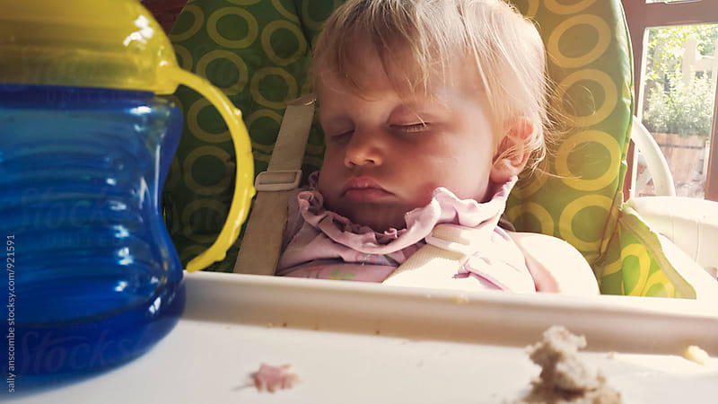 Baby girl asleep in her highchair  by sally anscombe for Stocksy United