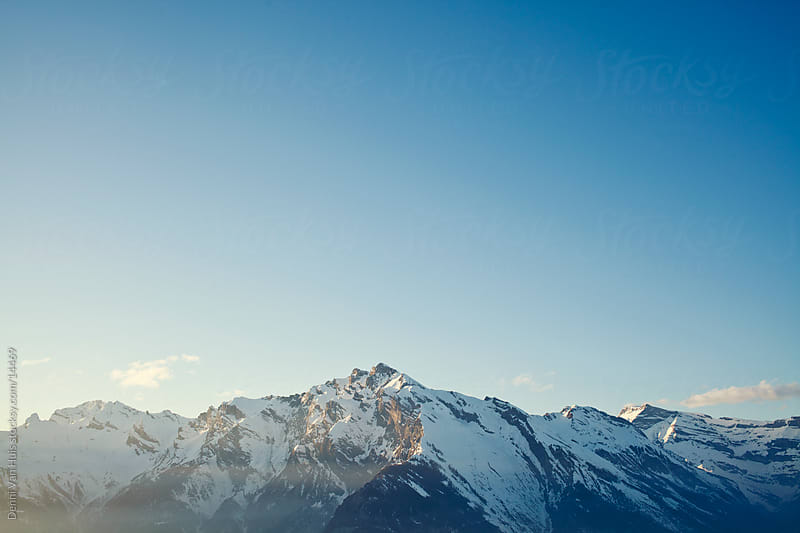 Snowy mountain tops in the distance by Denni Van Huis for Stocksy United