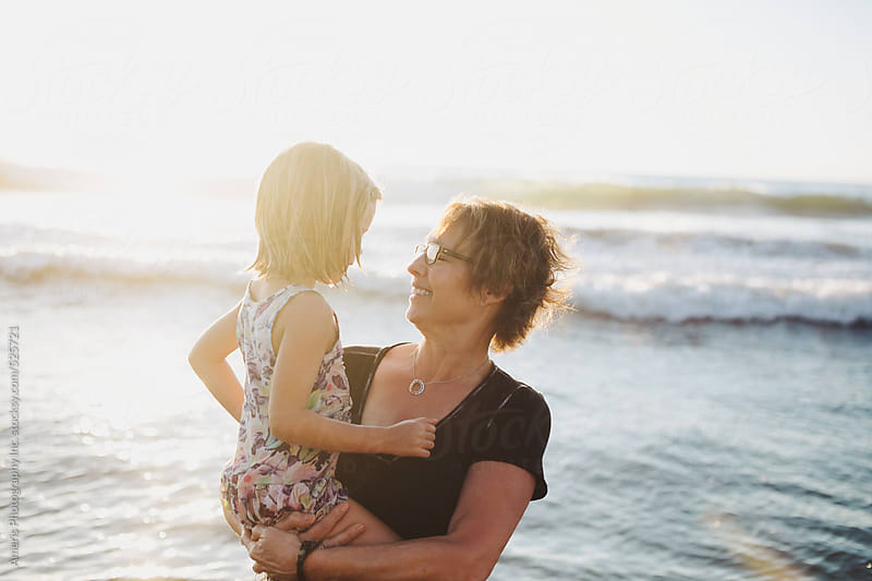 Fun, energetic grandma playing in ocean with young grandchild - girl - on beach at sunset by Rob and Julia Campbell for Stocksy United