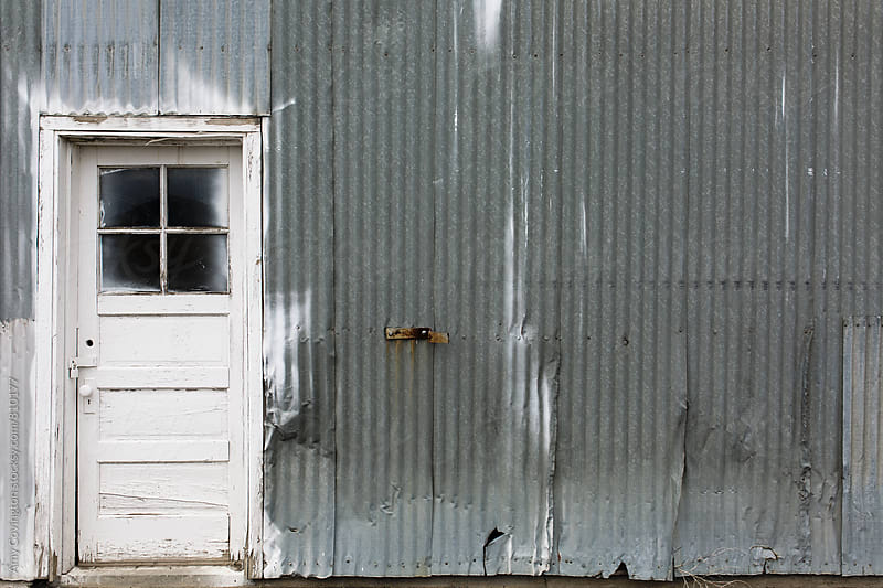 Building with metal siding and white door by Amy Covington for Stocksy United
