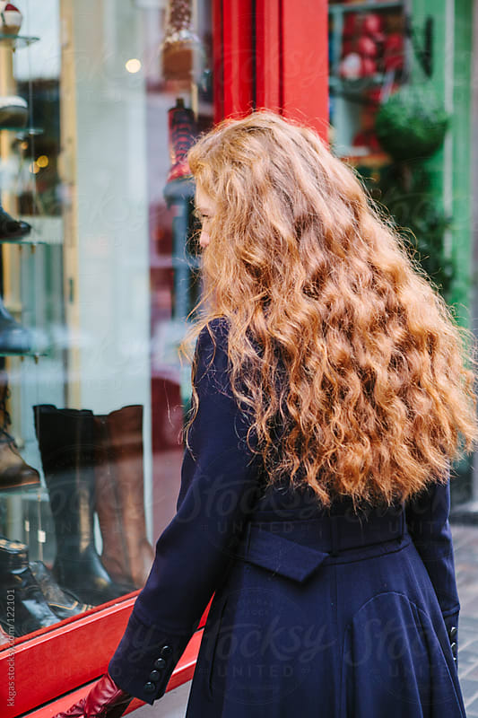 Red headed woman window shopping by kkgas for Stocksy United