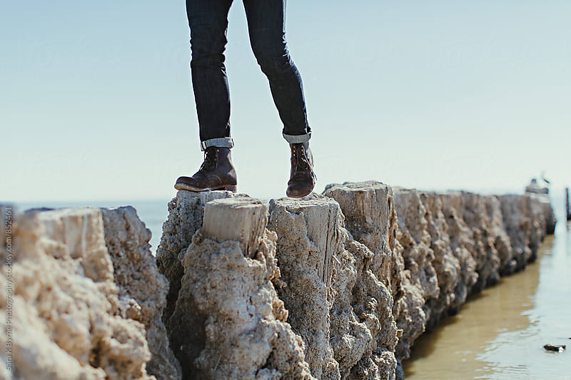 Man walking on sea fence by Sara K Byrne Photography for Stocksy United