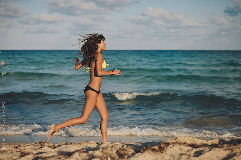 Sporty Young Woman Running along South Beach in Miami by Joselito Briones for Stocksy United