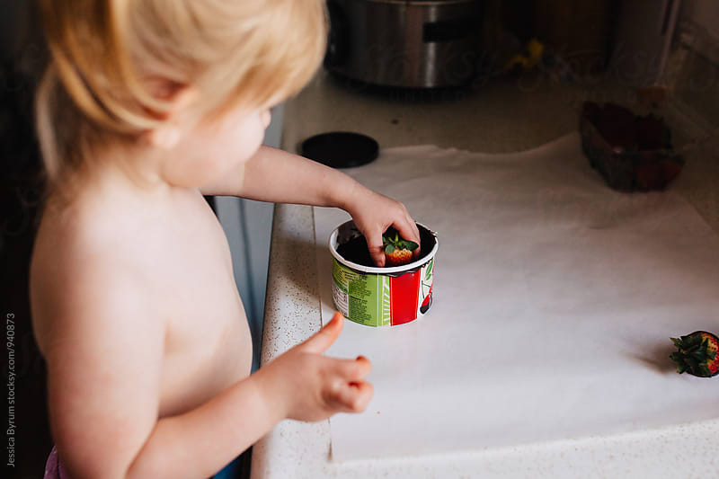 Small child making chocolate covered strawberries by Jessica Byrum for Stocksy United