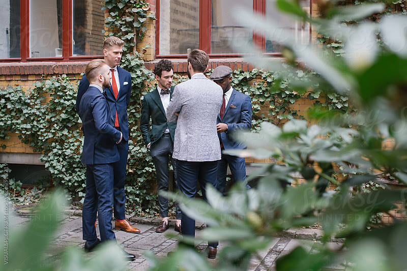 Group of Five Well-Dressed Young Men in Suits Standing in Courtyard by VISUALSPECTRUM for Stocksy United