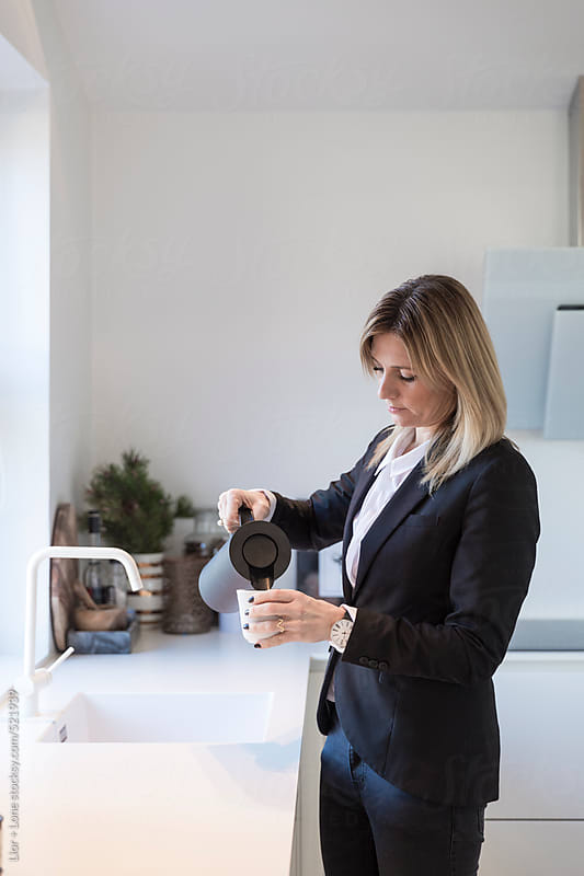 Businesswoman pouring tea in stylish white kitchen  by Lior + Lone for Stocksy United