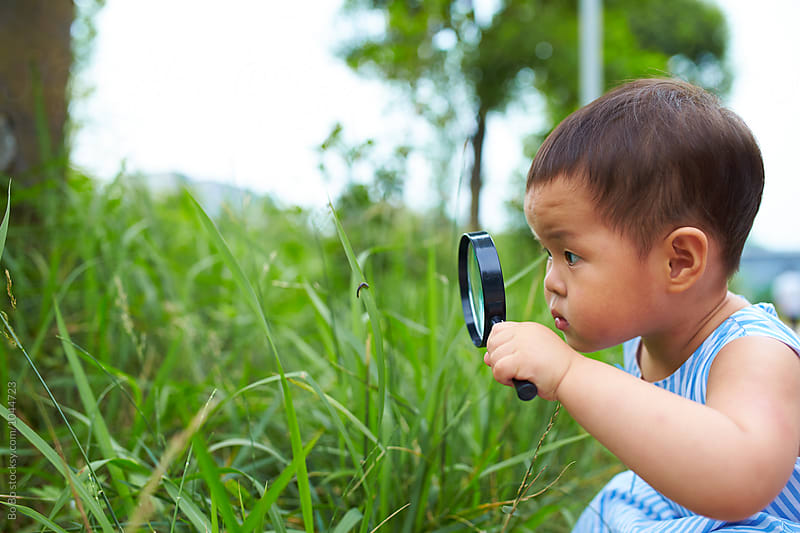 little girl using magnifying glass watch insect outdoor by cuiyan Liu for Stocksy United