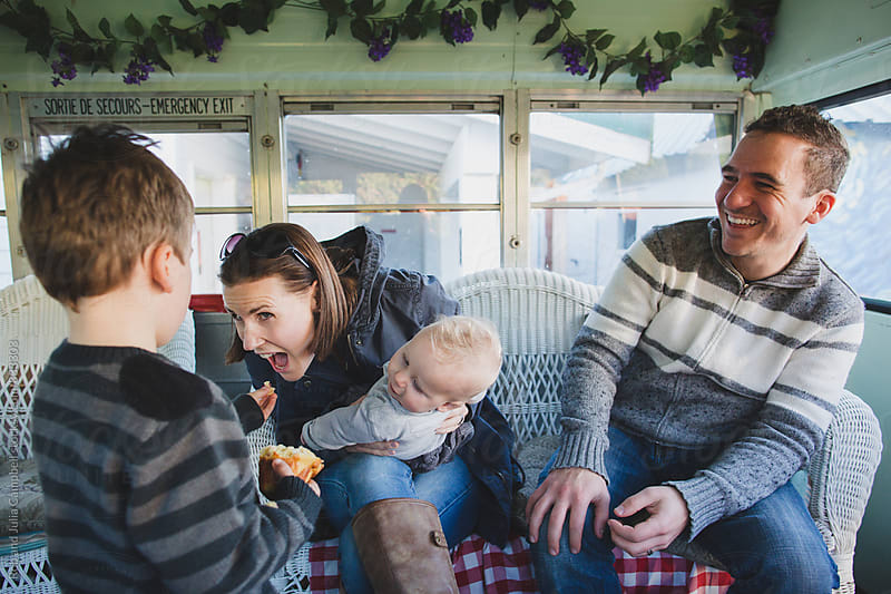 Mom eating from son's hand in random school bus by Rob and Julia Campbell for Stocksy United