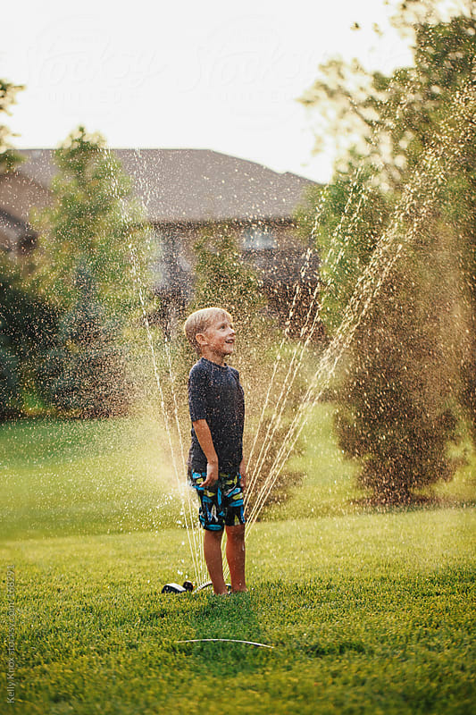 boy playing in a sprinkler by Kelly Knox for Stocksy United