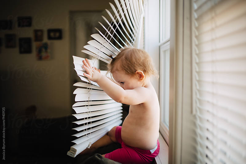 Toddler child playing with blinds by Jessica Byrum for Stocksy United