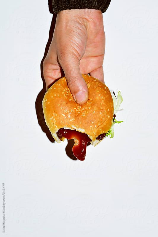 eating hamburguer  by juan moyano for Stocksy United