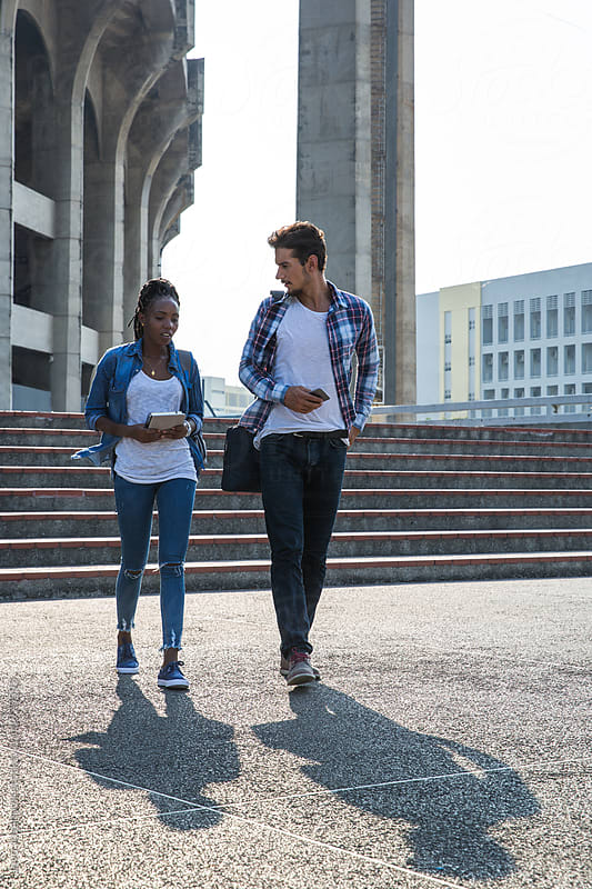 Two students walking together in campus by Jovo Jovanovic for Stocksy United