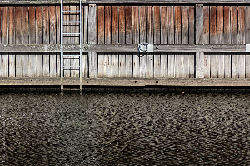 Ladder on an empty dock by Melanie Kintz for Stocksy United