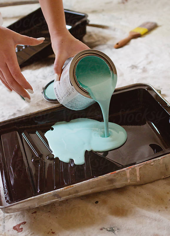 Young woman pours paint into a paint tray by Tana Teel for Stocksy United