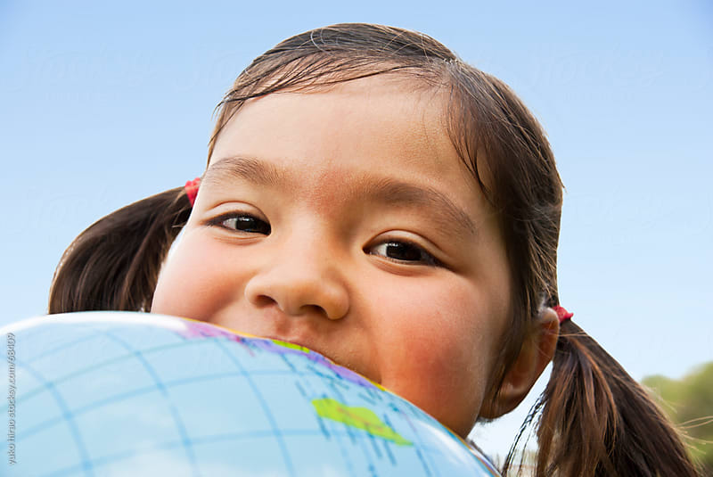 Smiley little girl with a world globe ball by yuko hirao for Stocksy United