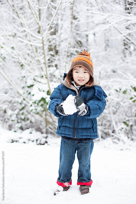 Asian boy playing snow in the winter by Suprijono Suharjoto for Stocksy United