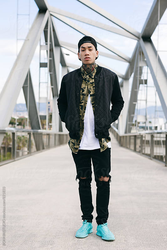 Portrait of an asian tattooed man standing on a modern bridge. by BONNINSTUDIO for Stocksy United