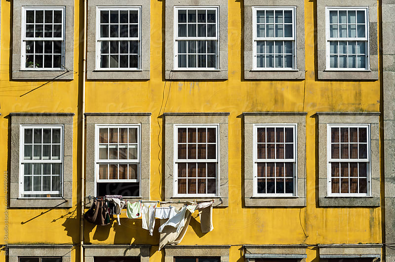 Yellow facade with the laundry, Oporto by Bisual Studio for Stocksy United