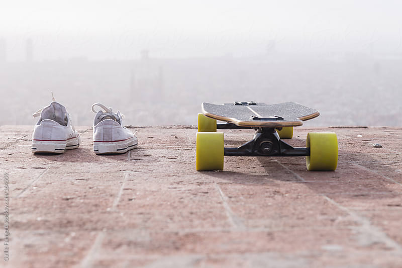 Skateboard and sneakers against of Barcelona by Guille Faingold for Stocksy United