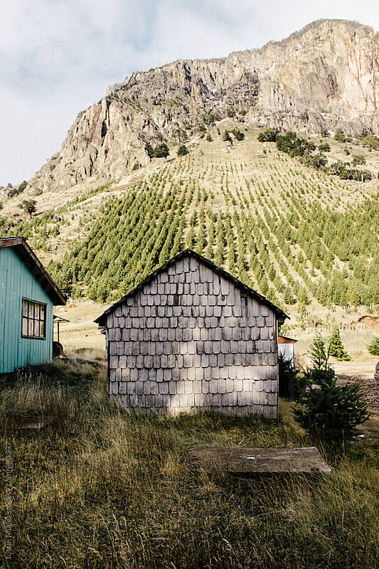 Small rustic shed standing underneath a mountain.  by Justin Mullet for Stocksy United