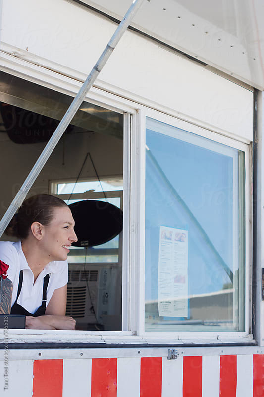 Food truck vendor looks out window of food truck by Tana Teel for Stocksy United