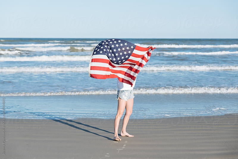 Woman holding American Flag in the wind on the beach. 4th of July at the ocean. by Jeremy Pawlowski for Stocksy United