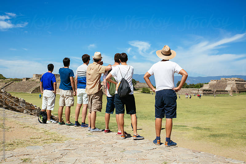 Group of people standing under sunlight looking to ancient ruins by Alejandro Moreno de Carlos for Stocksy United